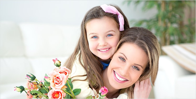 Mother and daughter smiling in a patio area with beautiful flowers